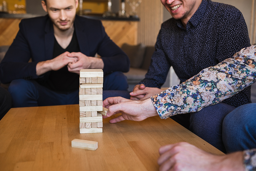 Guys play board game as part of their corporate team building activities