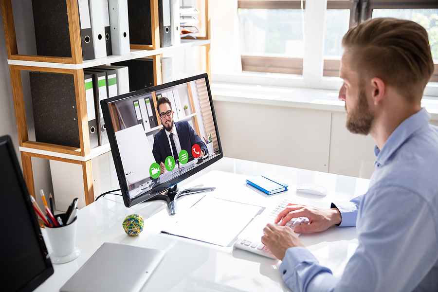 Businessman using video conferencing app in Melbourne with a coworker