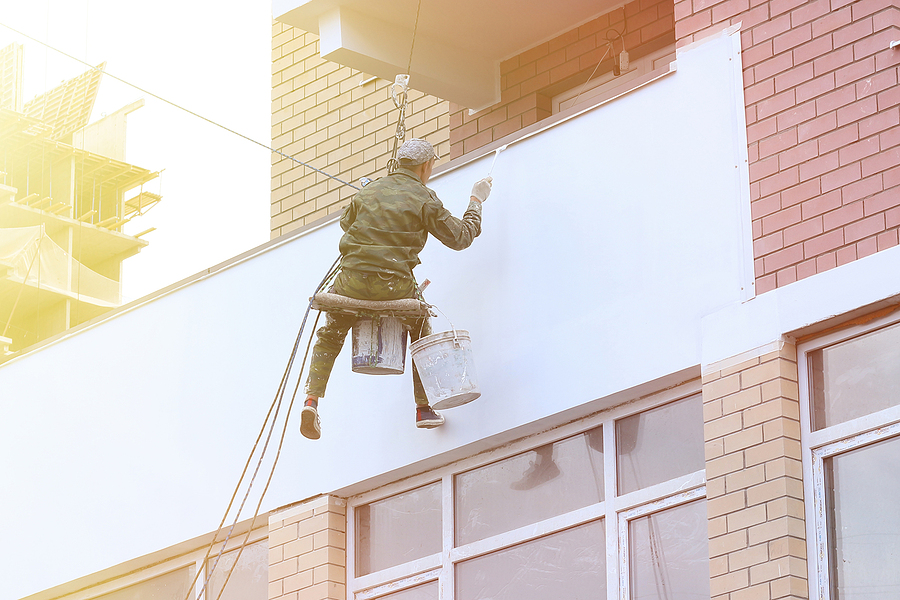 Worker of a commercial painting companies in Melbourne working on the outside wall of a high building