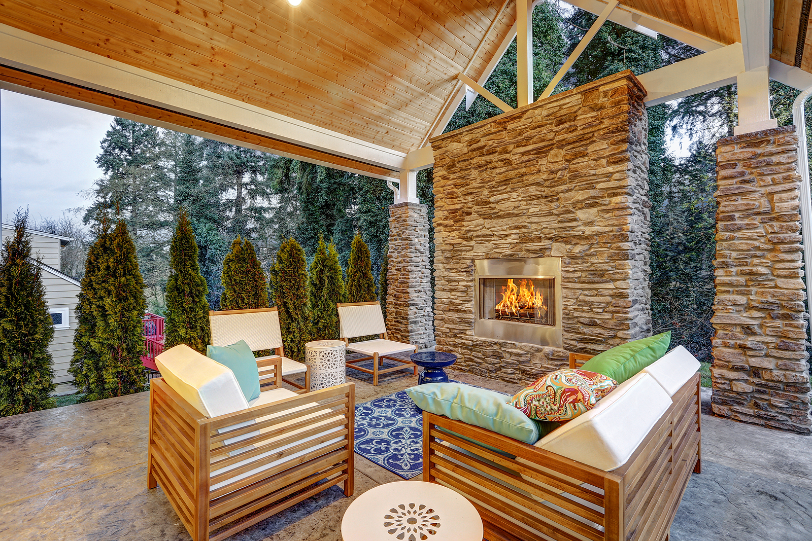 Chic covered patio with teak outdoor furniture